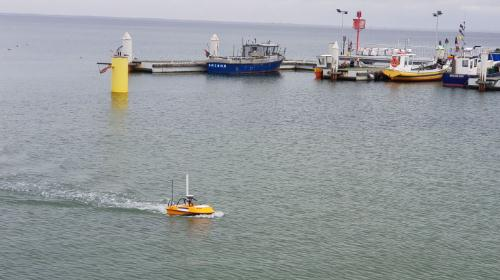 SL20 small unmanned surface vehicle sailing near a dock